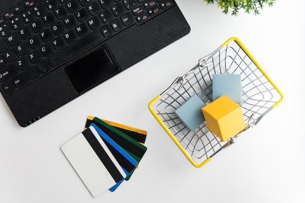 Bovenaanzicht van laptop, winkelmandje en creditcards. online winkelen en bezorgen concept Premium Foto