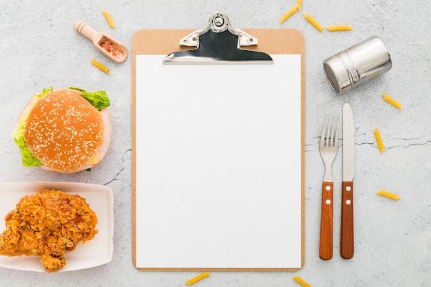 Bovenaanzicht van leeg menu met hamburger en gebakken kip Gratis Foto