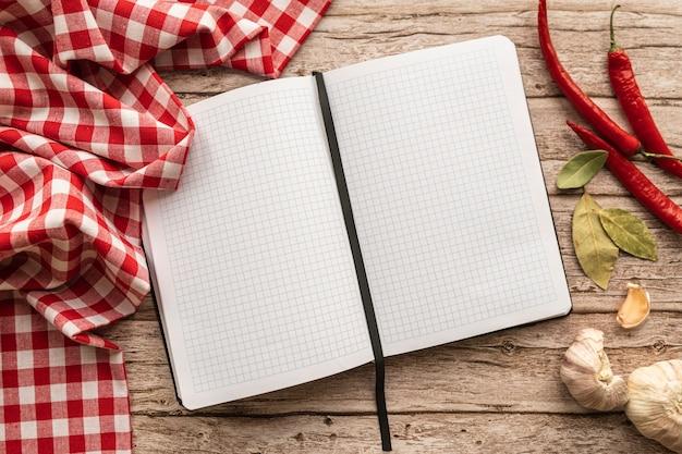 Bovenaanzicht van lege menuboek met tafellaken en chili pepers Gratis Foto