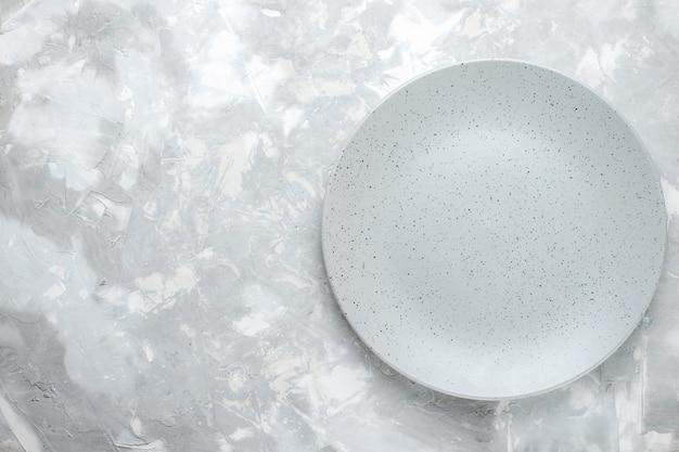 Bovenaanzicht van lege plaat grijze ronde gevormd op licht, plaat keuken Gratis Foto