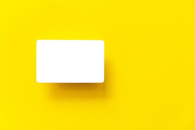 Bovenaanzicht van lege witte visitekaartje met schaduw op de achtergrond geel papier. Premium Foto