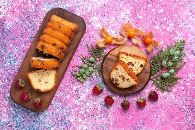 Bovenaanzicht van lekkere cake zoet en lekker gesneden met verse rode aardbeien op roze oppervlak Gratis Foto