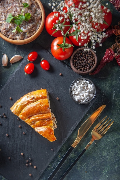 Bovenaanzicht van lekkere vleespastei met rode tomaten en gevuld vlees op donkere ondergrond Gratis Foto