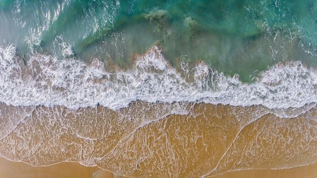 Bovenaanzicht van lucht van zee golf en zandstrand landschap. Premium Foto