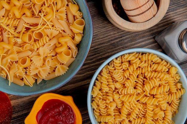 Bovenaanzicht van macaronis als rotini en anderen in kommen met ketchup zout zwarte peper op hout Gratis Foto