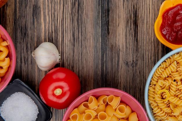 Bovenaanzicht van macaronis als rotini pijp-rigate en anderen in kommen met ketchup zout knoflooktomaat op hout Gratis Foto