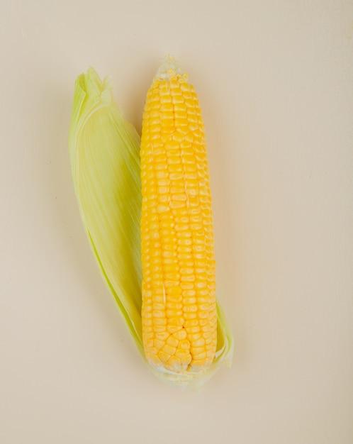Bovenaanzicht van maïs en zijn schelp op wit Gratis Foto