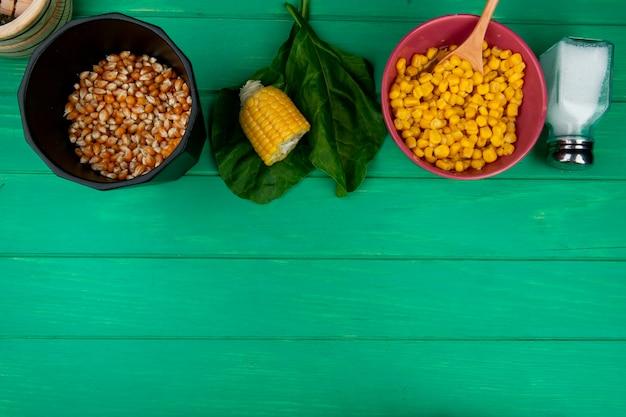 Bovenaanzicht van maïs zaden met gesneden maïs zout en spinazie op groen met kopie ruimte Gratis Foto