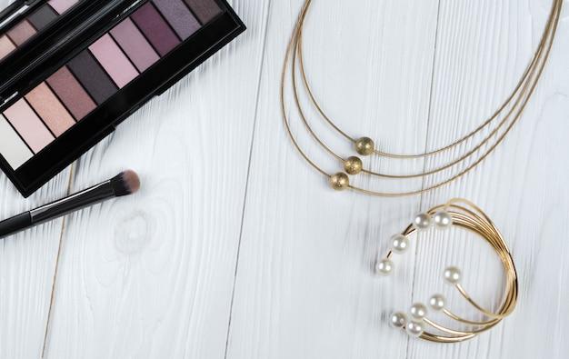Bovenaanzicht van make-up en gouden ketting en armband met parels accessoires op witte houten oppervlak Premium Foto