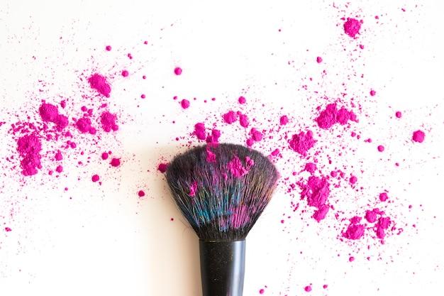 Bovenaanzicht van make-upborstel en roze gezichtspoeder Gratis Foto