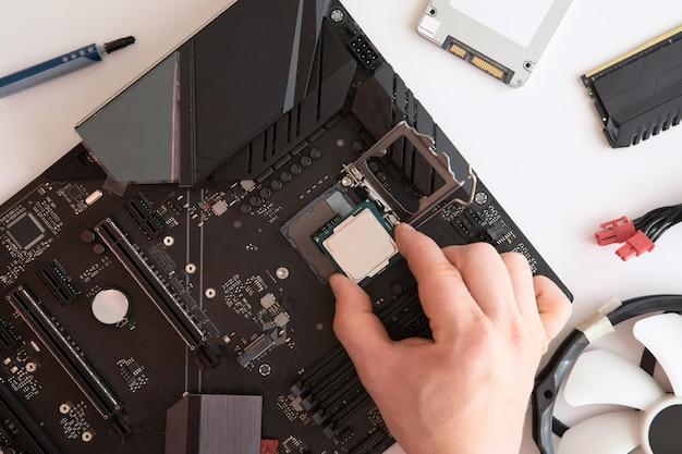 Bovenaanzicht van man handen zet cpu op moederbord, computeronderdelen, elektronica reparatie en upgrade kopie ruimte. moederbord, processor cpu, koeler, radiator, platliggend. Premium Foto
