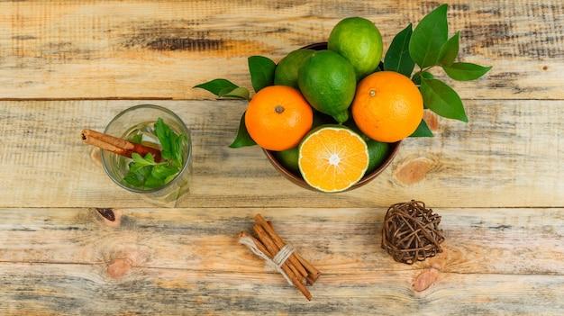 Bovenaanzicht van mandarijnen met kaneel en gefermenteerde drank op houten bord Gratis Foto