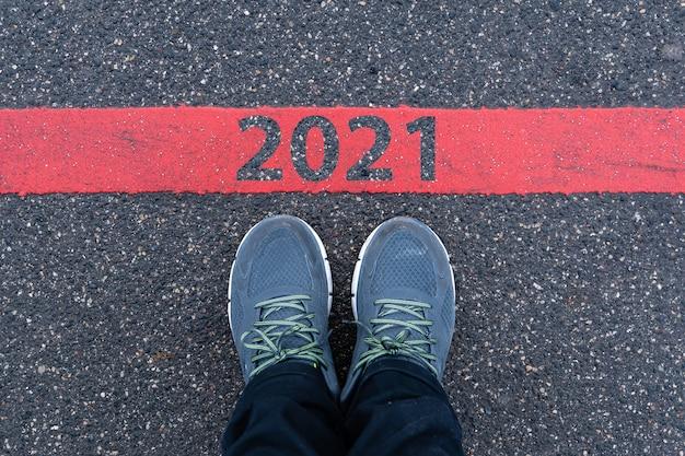 Bovenaanzicht van mannelijke sneakers op de asfaltweg met tekst 2021 op rode lijn, nieuwjaarsviering concept Premium Foto