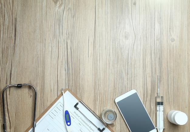 Bovenaanzicht van medisch onderzoeksrapport, mobiele telefoon en medische apparatuur op houten bureau Gratis Foto