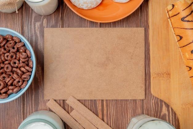 Bovenaanzicht van melkproducten als melk room zure geklonterde melk yoghurt soep met ontbijtgranen koekjes peperkoek en roll op snijplank rond karton op houten achtergrond met kopie ruimte Gratis Foto