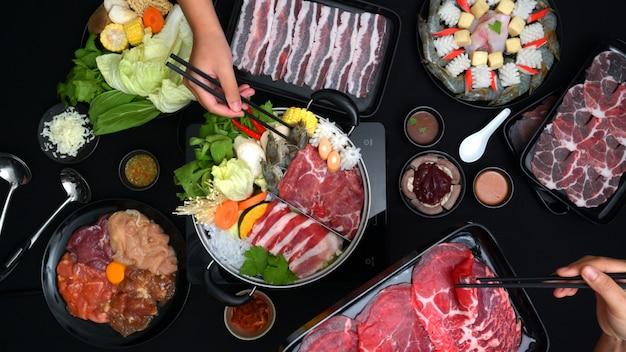 Bovenaanzicht van mensen die shabu-shabu eten in een hete pot met vers gesneden vlees, zeevruchten en groenten met zwarte achtergrond Premium Foto