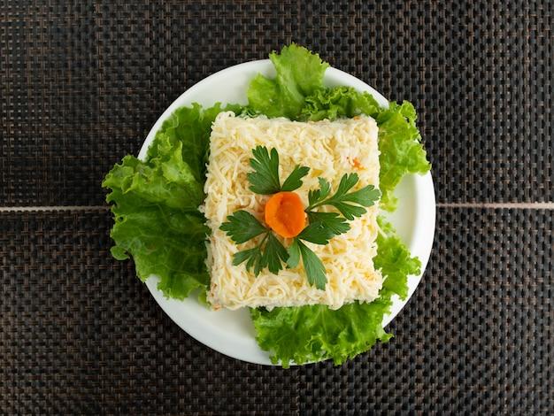 Bovenaanzicht van mimosa salade gegarneerd met peterselie en wortel bloem Gratis Foto