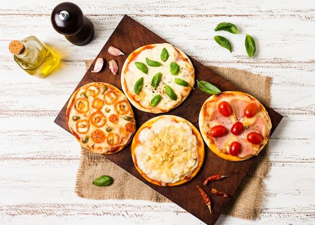 Bovenaanzicht van mini pizza op houten dienblad Premium Foto