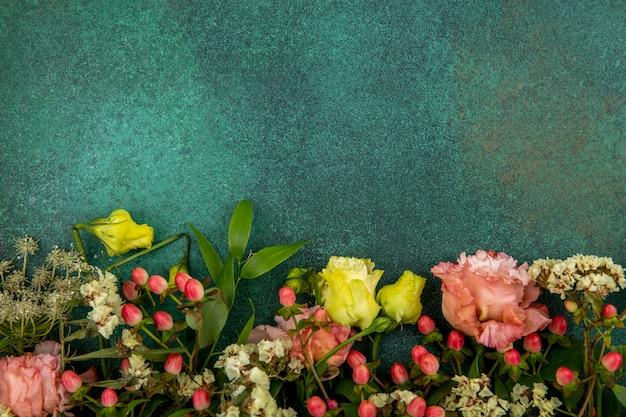 Bovenaanzicht van mooie en verse bloemen met bladeren op gre met kopie ruimte Gratis Foto