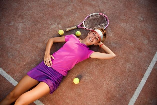 Bovenaanzicht van mooie lachende jong meisje in roze uniform en sportieve pet ligt op outdoor tennisbaan met veel ballen na een succesvolle training bij zonsondergang. Premium Foto