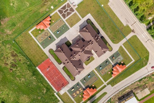 Bovenaanzicht van nieuw prescool-gebouw en tuin met nissen en groene gazons. Premium Foto