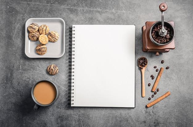 Bovenaanzicht van notebook met koffiekopje en grinder Gratis Foto