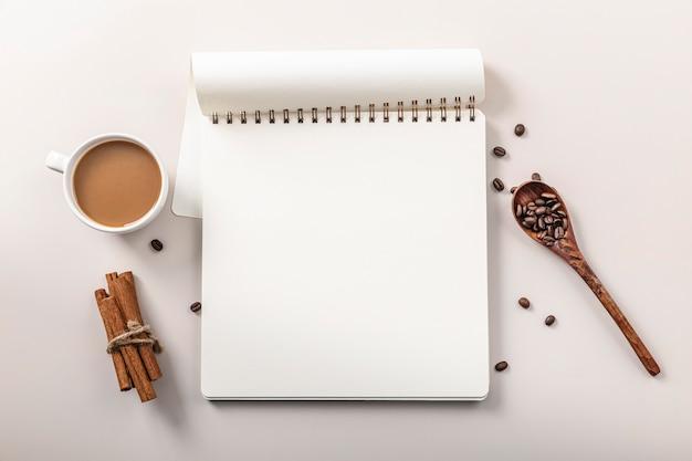 Bovenaanzicht van notebook met koffiekopje en kaneelstokjes Gratis Foto