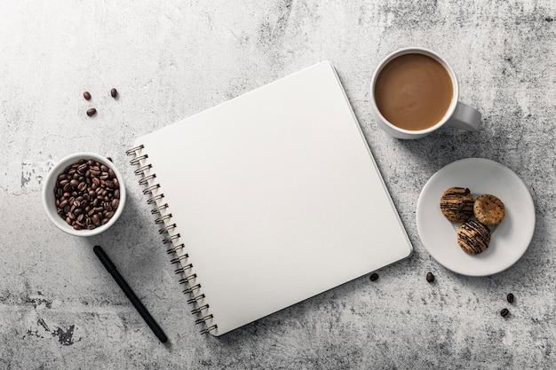 Bovenaanzicht van notebook met koffiekopje en koekjes op plaat Premium Foto