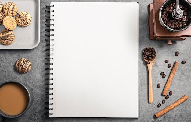 Bovenaanzicht van notebook met koffiemolen en koekjes Gratis Foto
