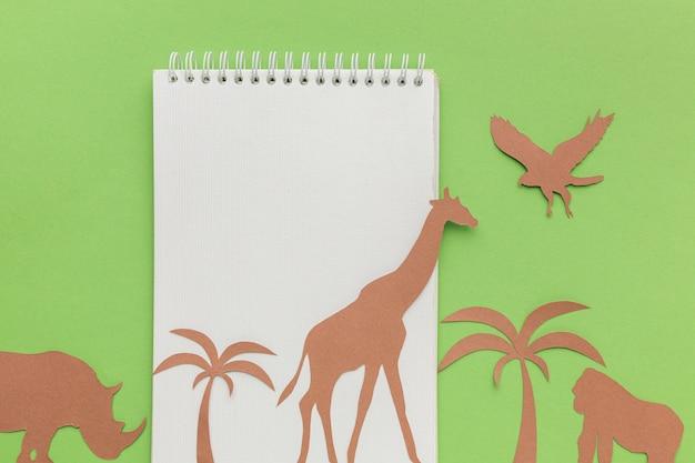 Bovenaanzicht van notitieboekje met papieren dieren voor dierendag Gratis Foto