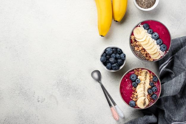 Bovenaanzicht van ontbijt desserts in kommen met bananen en lepels Gratis Foto