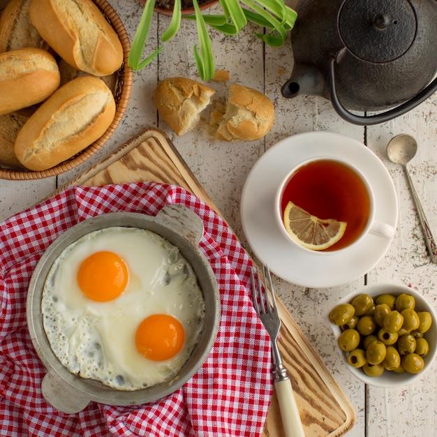Bovenaanzicht van ontbijt opstelling met eieren, olijven, brood en zwarte thee Gratis Foto