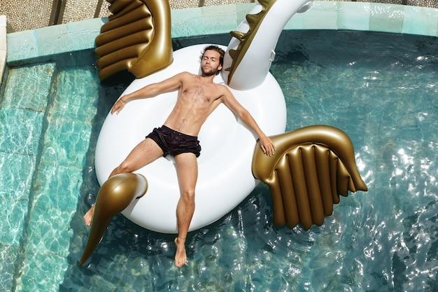 Bovenaanzicht van ontspannen en gelukkige jonge shirtless man drijvend in zwembad, liggend op luchtbed tijdens zijn langverwachte vakantie in tropisch land. Gratis Foto