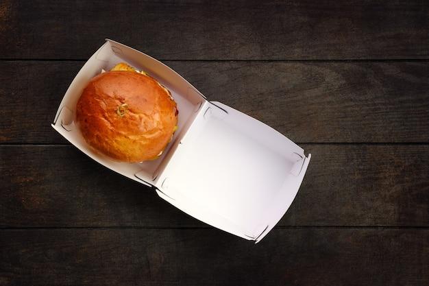 Bovenaanzicht van open afhaaldoos met hamburger op houten tafel Premium Foto