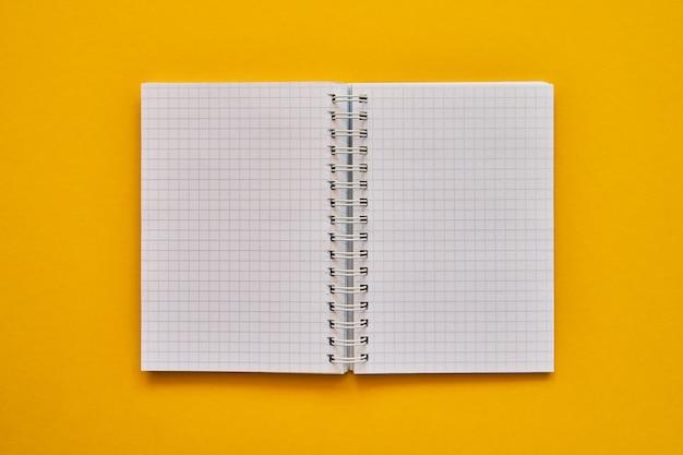 Bovenaanzicht van open laptop met blanco pagina's. schoolnotitieboekje op een gele achtergrond, spiraalvormig blocnote Premium Foto