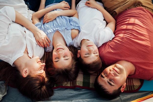 Bovenaanzicht van ouders met hun kinderen rusten in tent Gratis Foto