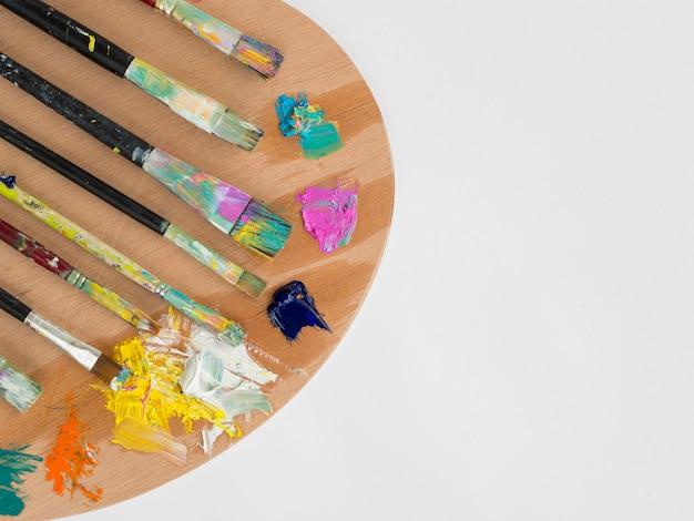 Bovenaanzicht van palet met verf en penselen Gratis Foto