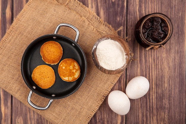 Bovenaanzicht van pannenkoeken in pan en bloem in kom op zak met eieren en aardbeienjam op houten achtergrond Gratis Foto