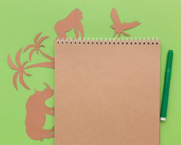 Bovenaanzicht van papieren dieren met notitieboekje en pen voor dierendag Gratis Foto