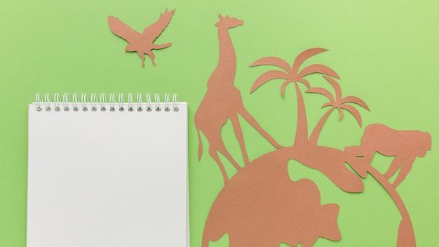 Bovenaanzicht van papieren dieren met planeet en notitieboekje voor dierendag Gratis Foto