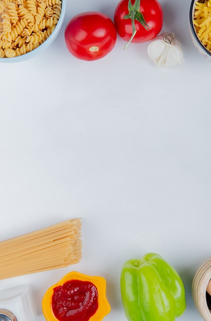 Bovenaanzicht van pasta in kommen, knoflook en tomaten Gratis Foto