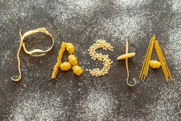 Bovenaanzicht van pasta woord op effen achtergrond Gratis Foto