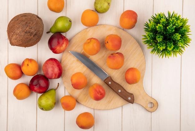 Bovenaanzicht van patroon van fruit als abrikozen met mes op snijplank en patroon van peren kokos perziken met bloem op houten achtergrond Gratis Foto