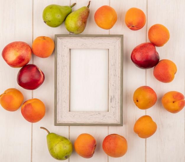 Bovenaanzicht van patroon van fruit als abrikozenperzik en peer rond frame op houten achtergrond met kopie ruimte Gratis Foto