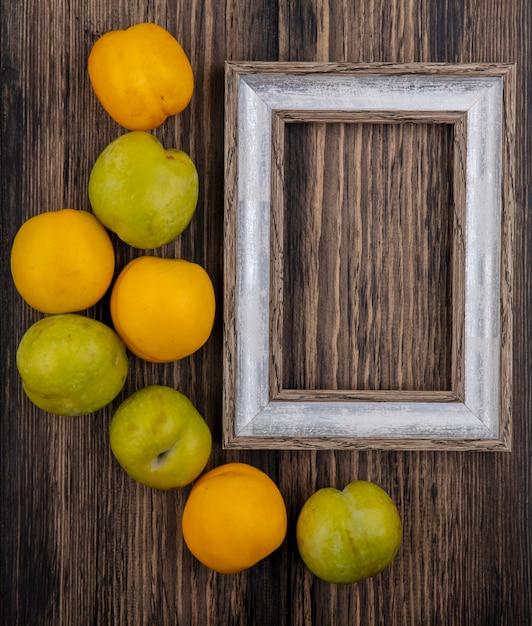 Bovenaanzicht van patroon van fruit als plukken en nectacots met frame op houten achtergrond met kopie ruimte Gratis Foto