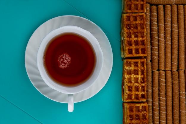 Bovenaanzicht van patroon van knapperige stokken en gebak met kopje thee op blauwe achtergrond Gratis Foto