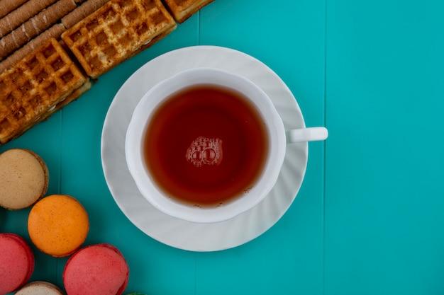 Bovenaanzicht van patroon van koekjes en knapperige stokkencakes met kop thee op blauwe achtergrond met exemplaarruimte Gratis Foto