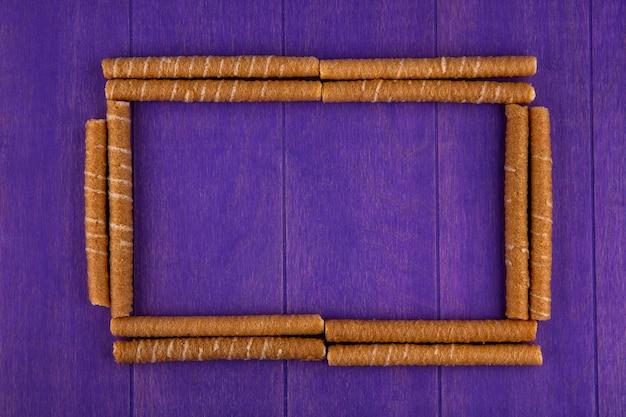 Bovenaanzicht van patroon van krokante stokken in vierkante vorm op paarse achtergrond met kopie ruimte Gratis Foto