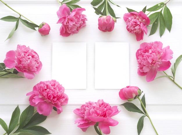 Bovenaanzicht van pioenroos bloem frame met helder wit papier Gratis Foto