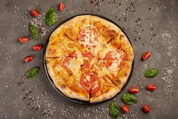 Bovenaanzicht van pizza met tomaten en peper Gratis Foto